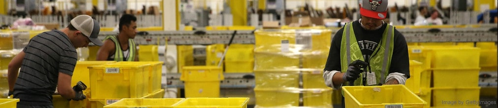 Two employee sorting yellow plastic boxes in Amazon fulfillment center.
