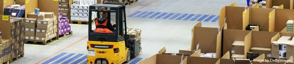 An employee in Amazon fulfillment center moving a pallet of boxes using a forklift