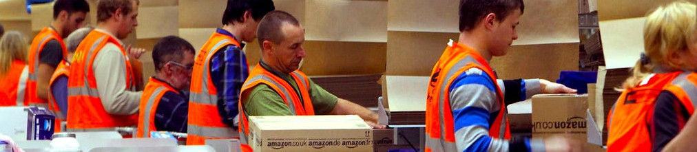 Employees in orange vests sorting boxes in Amazon fulfillment center