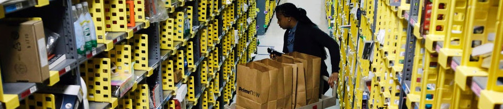 Amazon employee pushing a trolley with carton bags between shelves filled with different packages