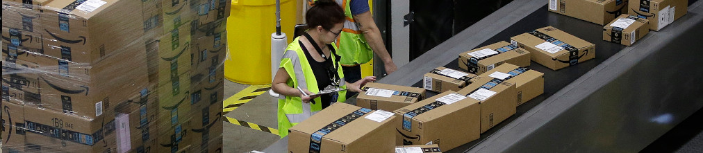 Employee sorting boxes on transporter tape of Amazon fulfillment center