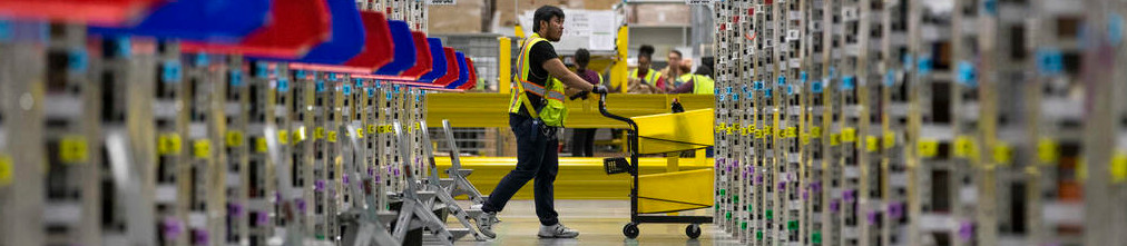 Amazon employee rolling a cart through fulfilment center