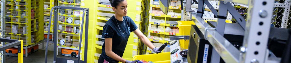Amazon employee sorting yellow boxes in the fulfillment center