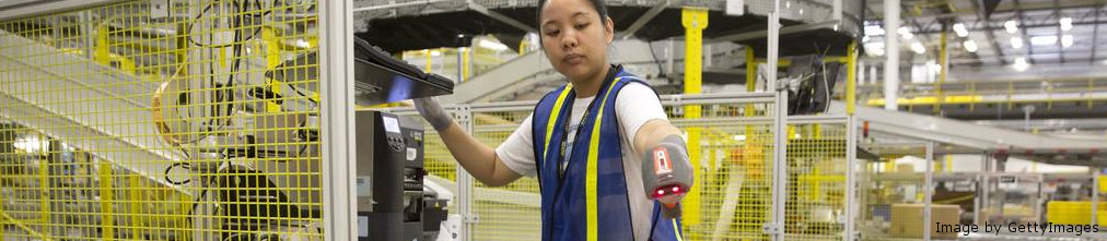 Amazon employee scanning boxes on the conveyor tape of the fulfillment center