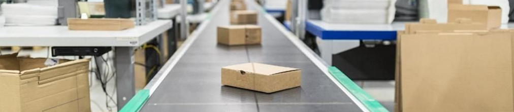 Cardboard boxes moving on transporter tape in Amazon fulfillment center