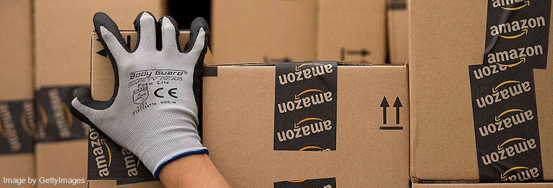 Amazon employee in gray glove picking up a box with Amazon logo stickers