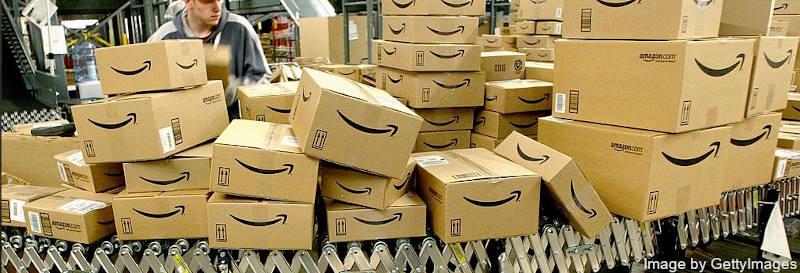 Amazon employee watching at conveyor belt full of boxes with Amazon.com logos